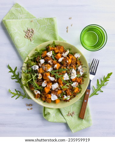 Pumpkin quinoa salad with fresh arugula and sunflower seeds - stock photo