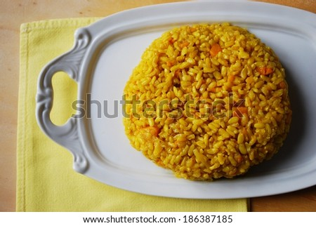 Pumpkin risotto made with brown rice, onion and curry served on white dish