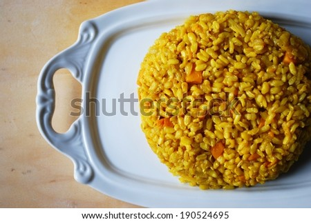Pumpkin risotto made with brown rice, onion and curry served on white dish - stock photo