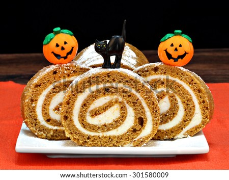 Pumpkin roll cake decorated with pumpkins and a black cat for Halloween.