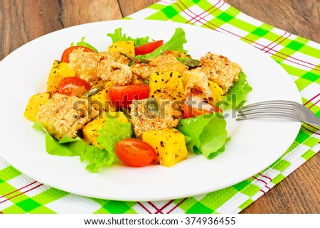 Pumpkin Salad, Suluguni Fried in Sesame, Pumpkin Seeds, Cherry Tomatoes and Lettuce Leaves Studio Photo