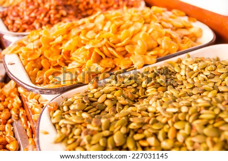 pumpkin seeds and fried broad beans in market stand selective focus - stock photo