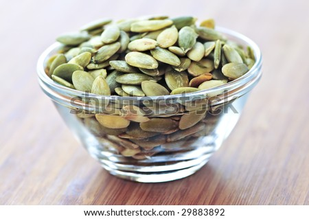 Pumpkin seeds close up in glass bowl - stock photo