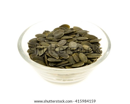 pumpkin seeds  in a glass bowl. Isolated on white.