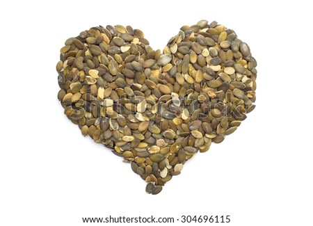 Pumpkin seeds in a heart shape, isolated on a white background - stock photo
