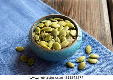 Pumpkin seeds in blue bowl close up - stock photo