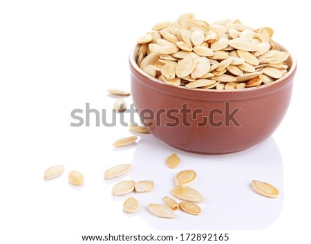 Pumpkin seeds in bowl isolated on white - stock photo