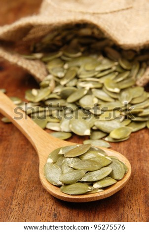 Pumpkin seeds on a wood spoon - stock photo