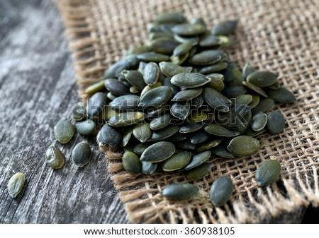 pumpkin seeds on wooden surface - stock photo