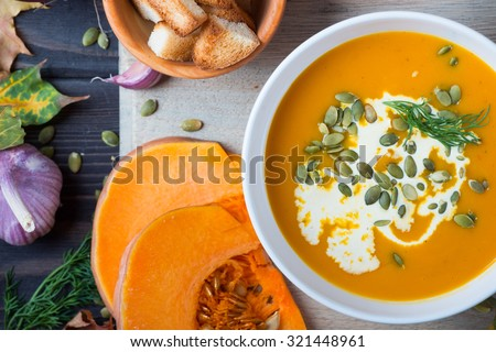 Pumpkin soup among autumn leaves on a wooden table  - stock photo