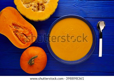 Pumpkin soup cream on a wooden table and ingredients - stock photo