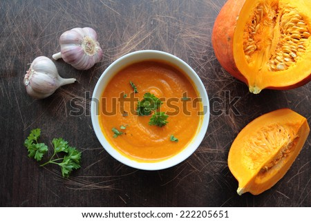 Pumpkin soup in a bowl with fresh pumpkins, garlic and parsley herbs - stock photo