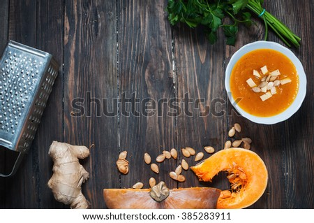 Pumpkin soup in a bowl with fresh pumpkins, ginger and parsley herbs. - stock photo