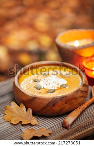 Pumpkin soup in a rustic bowl outside in autumn - stock photo