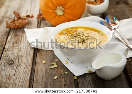 Pumpkin soup in a white cup on wooden background - stock photo