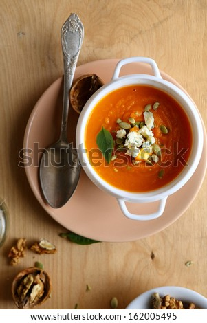 pumpkin soup in a white tureen, food top view - stock photo