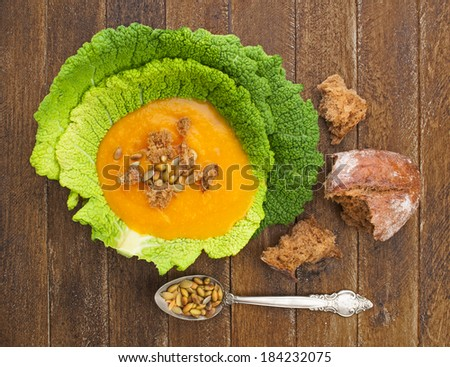 Pumpkin soup in savoy cabbage leafs on wooden background