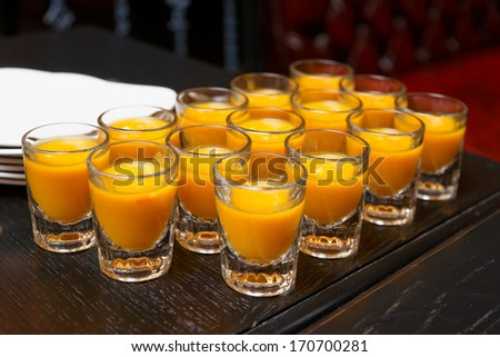 Pumpkin soup in shot glasses served at a banquet - stock photo