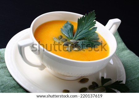 Pumpkin soup in white plate on black background - stock photo