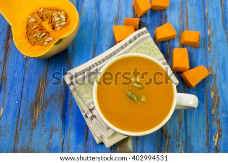Pumpkin soup puree, blue wooden table, raw pumpkin. - stock photo
