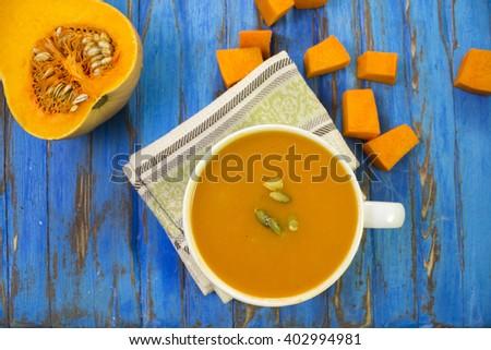 Pumpkin soup puree, pumpkin raw wooden blue table. - stock photo