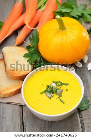 Pumpkin soup, raw pumpkin, carrots and toasted bread on rustic wooden table - stock photo