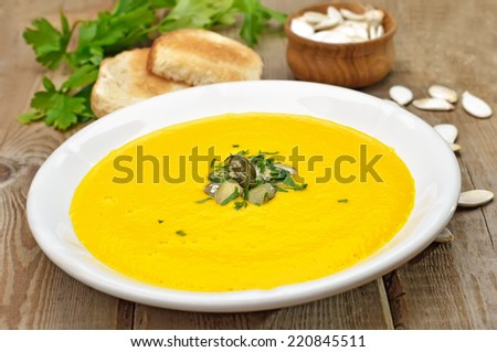 Pumpkin soup, seeds and toasts on rustic wooden table - stock photo