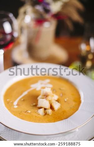 Pumpkin soup with bread, in white bowl on wooden  table. - stock photo
