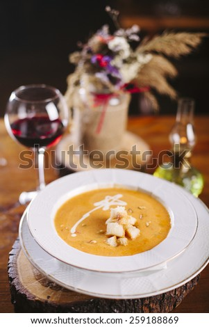 Pumpkin soup with bread, in white bowl on wooden  table, with glass of wine.  - stock photo