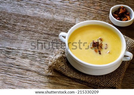 pumpkin soup with chanterelles on a dark wood background. tinting. selective focus on chanterelle mushrooms in the soup - stock photo