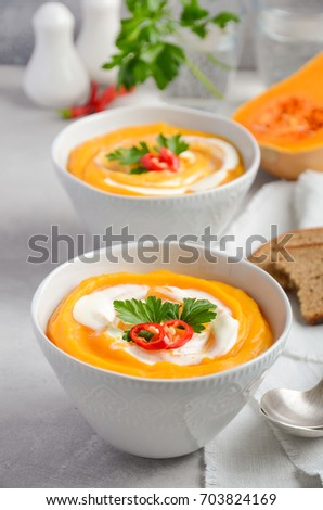 Pumpkin soup with cream and parsley on a grey concrete or stone background, selective focus