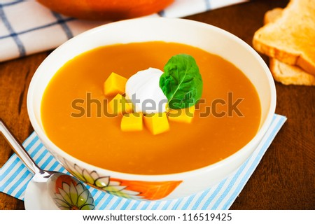 Pumpkin soup with cream in a bowl with painted flower and toast as a garnish on wood table - stock photo