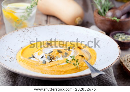 Pumpkin soup with cream, seeds and thyme on a wooden background - stock photo