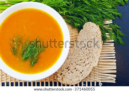 Pumpkin soup with dill and bread on a mat - stock photo