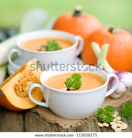 Pumpkin soup with fresh pumpkins - stock photo