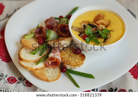 Pumpkin soup with fried garlic, chiken and mushrooms - stock photo