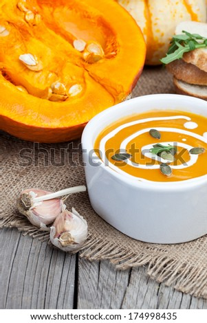Pumpkin soup with garlic and fresh cream on dark wooden table - stock photo