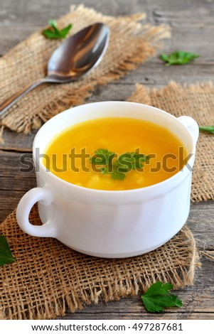 Pumpkin soup with potatoes, rice and parsley. Simple pumpkin soup in bowl on old wooden background, spoon, burlap. Vegetarian dish. Rustic style. Closeup