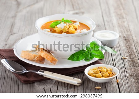 Pumpkin soup with pumpkin Seeds, cream and basil on rustic wooden background, selective focus - stock photo