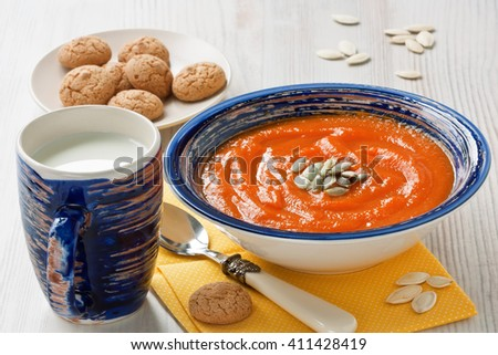 Pumpkin soup with seeds, cup milk and cookies on wooden background/Pumpkin soup  - stock photo