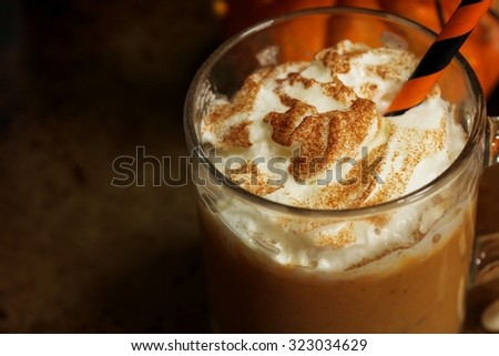 Pumpkin spice latte close up on dark moody background, selective focus