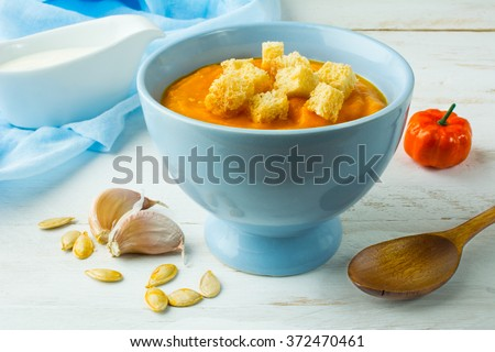 Pumpkin squash vegetable soup with garlic croutons in a blue bowl on white wooden background. Pumpkin soup. Squash soup. Soup. Creamy soup. Vegetable soup  - stock photo