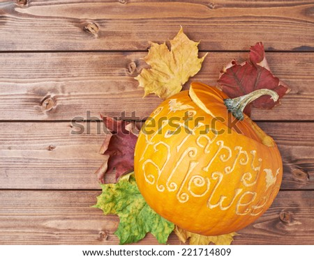 Pumpkin with the words Happy halloween carved over its surface over the colorful maple leaves and wooden background surface composition - stock photo
