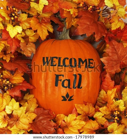 "pumpkin with ""welcome Fall"" surrounded by autumn leaves - stock photo"