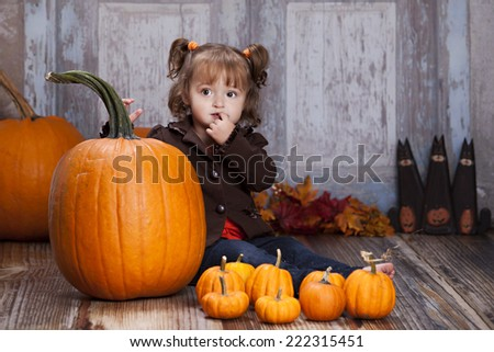 Pumpkins.  Adorable girl sitting next to some pumpkins.