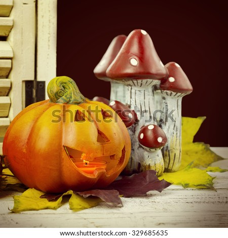 pumpkins and autumn leaves on wooden background