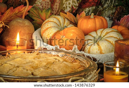Pumpkins and cake on candle light still life - stock photo