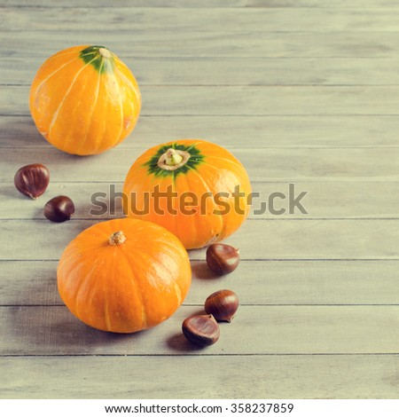 Pumpkins and nuts on a wooden background. Selective focus.
