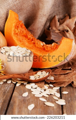 Pumpkins and pumpkin seeds in bowl on wooden background - stock photo