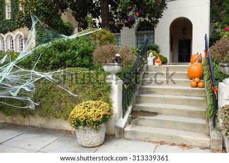 Pumpkins and scary decorations on front steps of home during Halloween / Thanksgiving season  - stock photo